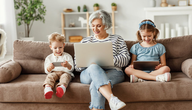 Senior woman with grandchildren using gadgets at home.