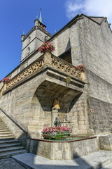 Saint-Laurent collegiate church and fountain in Estavayer-le-lac by day, Fribourg, Switzerland