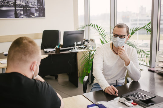 an office worker in a protective mask talks to a client