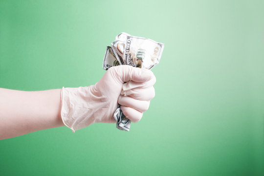hand in a rubber white medical disposable glove clenches wrinkled dollar bills in a fist on a green background copy space