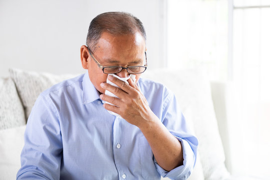 Sick asian old man using tissue paper close mouth while cough, sitting on sofa at home. Senior healthcare concept.