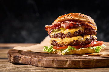 Fototapeta Juicy American burger, hamburger or cheeseburger with two beef patties, with sauce and basked on a black background. Concept of American fast food. Copy space obraz