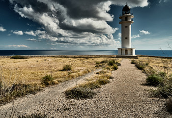 Lighthouse on the Formentera island, Spain, the blue sky with white clouds, without people, rocks, stones, sunny weather Wall mural