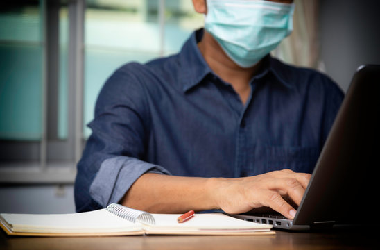 Male employee wearing a health mask Preventing corona virus infection covid-19, concept of working from home and social distancing.