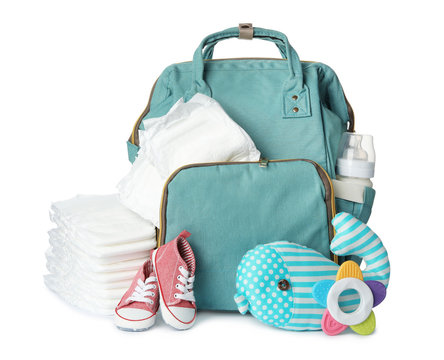 Backpack with disposable diapers and child's accessories on white background