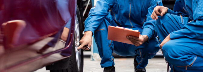 banner of automotive mechanic men checking at  car tyre rubber condition needed for replacement, man pointing hand at wheel following maintenance checklist document, after service at auto repair shop