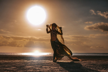 silhouette of young stylish tribal woman in turban outdoors at sunset
