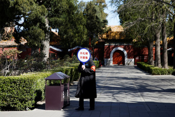Staff member holds a sign advising visitors to avoid clustering at Jingshan Park, amid the novel coronavirus disease (COVID-19) outbreak in the country, in Beijing