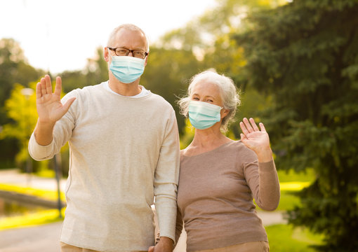 health, quarantine and pandemic concept - senior couple wearing protective medical mask for protection from virus waving hands at park