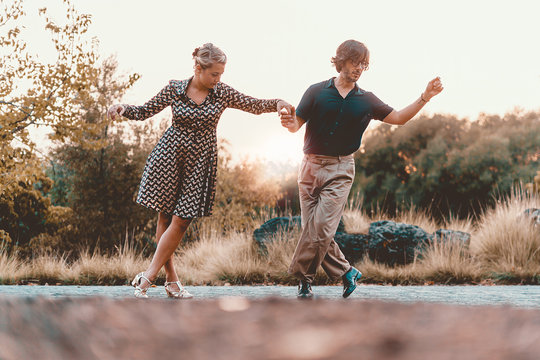 Couple of friends dancing swing in the sunset at the park. Couple of young people having fun dancing lindy hop Lifestyle concept.