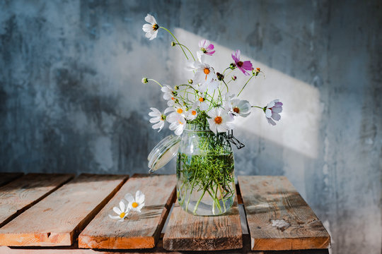 Beautiful bouquets of wildflowers on a wooden table on a cold concrete wall background.