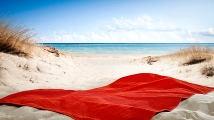 Red towel on beach and free space for your decoration.