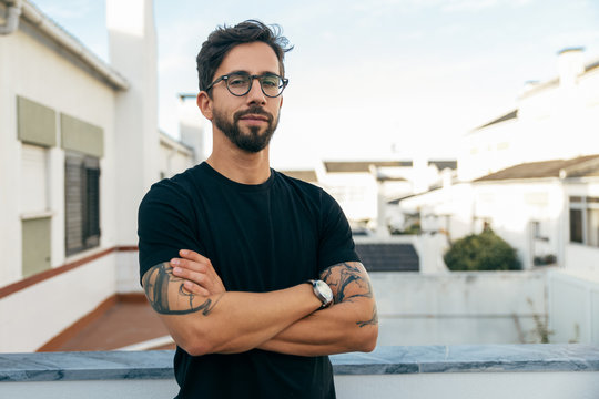 Confident stylish guy with tattoos posing on apartment balcony or terrace. Young man in glasses standing outside with arms crossed and looking at camera. Male portrait concept