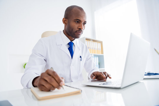 Photo of family doc dark skin guy watch notebook webinar medical reform cov viral news noting changing personal planner wear white lab coat sitting chair table office clinic indoors