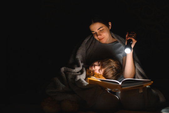 Happy family. Time for stories. Delighted happy cute mother and son enjoying a book before sleeping and using a flashlight.