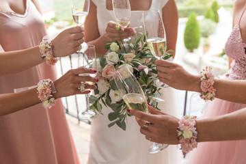 Novia con ramo de flores y damas de honor brindan con copas de champan. Fotobehang