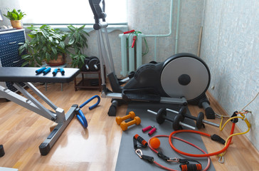 Equipment for home workouts: an elliptical trainer, a set of dumbbells, rubber espadars, sports bench and a yoga mat. Home fitness concept. Activity during Coronavirus pandemic quarantine isolation