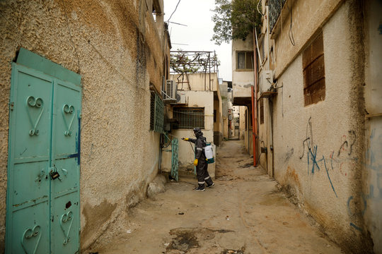 A worker sanitizes the exterior of a house in al-Fari'ah refugee camp in the Israeli-occupied West Bank