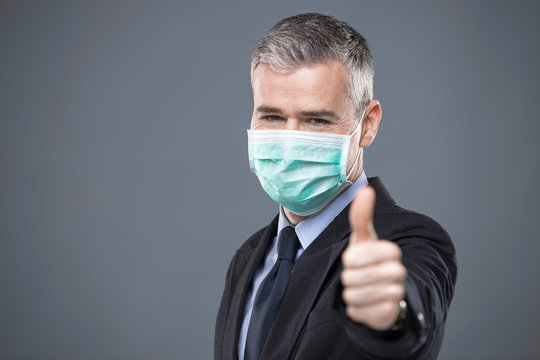 Businessman in face mask giving a thumbs up