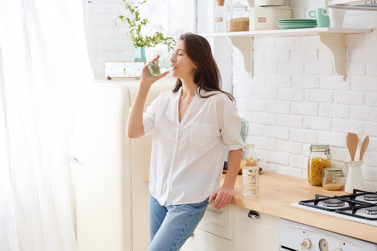 Gorgeous woman drinking water in her kitchen