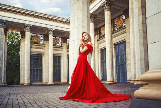 Beautiful blonde girl in a red long dress on a background of architecture, columns