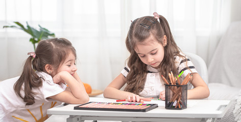 Children sit at the table and do their homework. The child learns at home. Home schooling.