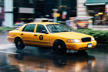 Papiers peints New York TAXI Yellow taxi driving through the streets of New York on a rainy day. Dynamic image