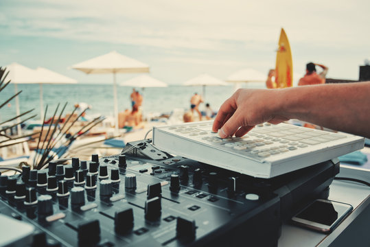 DJ hand and mixer close-up. Summer music party on the beach. On a blurred background people and the sea