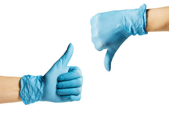 Hands in a medical glove show thumb up down . On a white isolated background