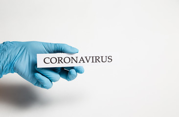 A hand in a medical glove holds the inscription coronavirus on a white background