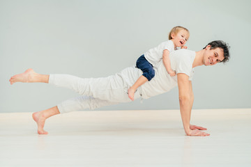 Tuinposter Ontspanning Positive sportive father doing pilates, yoga exercise, workout at home in floor with his little baby son having fun, excited emotion, play together, communication concept.
