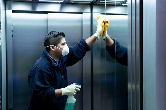 coronavirus. cleaning staff disinfecting elevator to avoid contagion