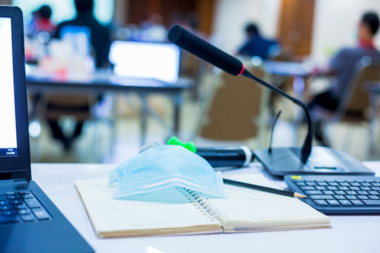 selective focus to wireless microphones and mask with blurry pencil on notebook in a meeting room. Equipment used in meetings and prevent Coronavirus Covid-19 in business conference room.