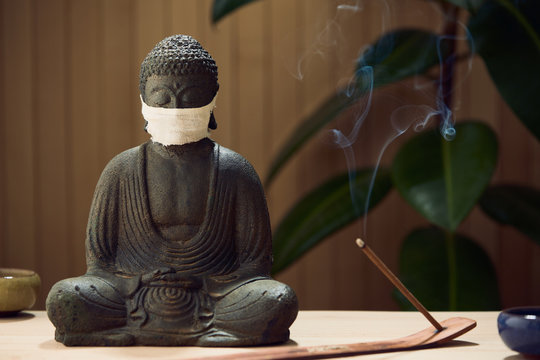 Buddha in a medical mask against a virus