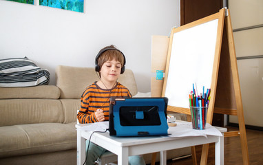 Happy little boy attending online classes from home. Child using digital tablet and headsets for connecting with teacher and schoolmates. School education and social distance. Distance Learning