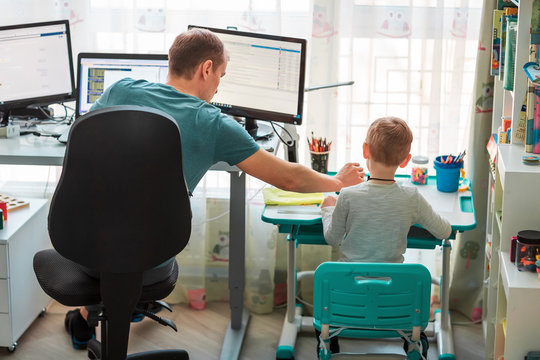 Father with kid working from home during quarantine. Stay at home, work from home concept during coronavirus pandemic