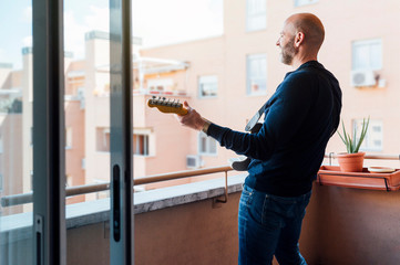 Man in a hat with a beard plays the guitar on the balcony in the summer. Side view. Covid - 19 Fotomurales