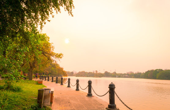 Lake side public park in summer evening. Garden footpath park lane illuminated by sunset sunlight. Red and orange color in landscape scene. Sun setting. Dhakuria lake Town Kolkata West Bengal India