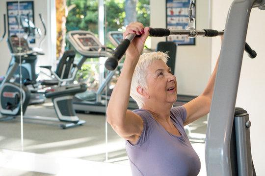 Active Senior woman exercising at the gym