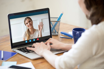 Back view of young woman sit at desk at home have video call with smiling millennial sister or friend, happy girlfriends talk chat using modern wireless internet connection, speak on webcam on laptop