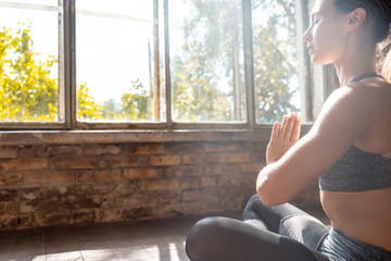 Mindful calm fit sporty healthy woman sit in lotus pose doing yoga exercise breathing fresh air meditating in sunny studio indoors, stress free peace of mind concept, copy space, close up side view
