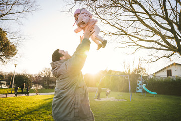 Father and female child at the park - Portrait of a dad having fun with his daughter holding her in his arms - Copy space - Moment of happiness and intimacy