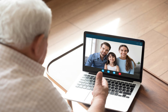 Back view of elderly grandfather talk chat on video call on computer with family and granddaughter, mature granddad have online conversation using webcam on laptop with happy relatives