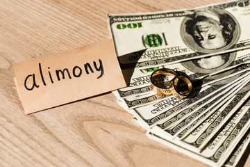 paper with alimony lettering near dollar banknotes and engagement rings