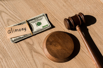top view of gavel near dollar banknotes and paper with alimony lettering on wooden desk