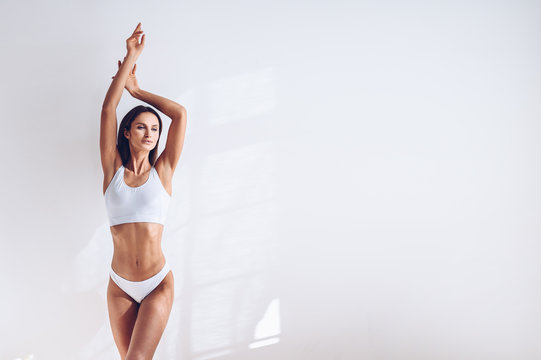 Young fit woman in white lingerie on white background isolated. Muscular slim attractive female with flat belly. Copy space for text. Body care, healthy and sporty life, hair removal, yoga concept