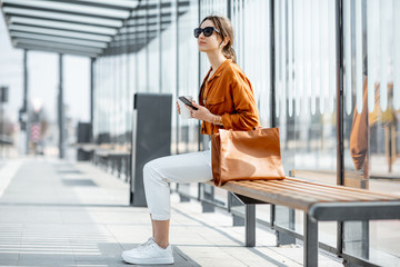 Young stylish woman waiting for the public transport, sitting with phone and coffee at the stop outdoors. Urban business travel and transportation concept Fotomurales