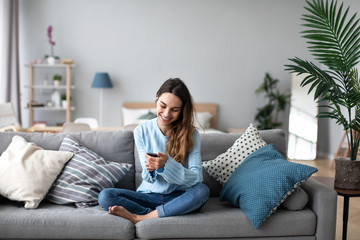 Online chat. Smiling woman talking on smartphone with friends while sitting on sofa at home. Wall mural