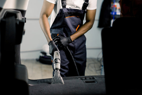Professional cleaning of car interior by wet vacuum machine. Clopped image of male African auto service worker cleaning the trunk of the car with vacuum cleaner. View from the car