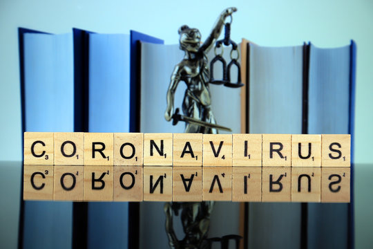 WROCLAW, POLAND - MARCH 30, 2020: The word CORONAVIRUS made of wooden letters, and symbol of law and justice in the background. Coronavirus (COVID-19) global disease 2020.